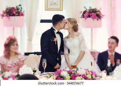 Romantic happy handsome groom kissing beautiful white dress bride at wedding reception