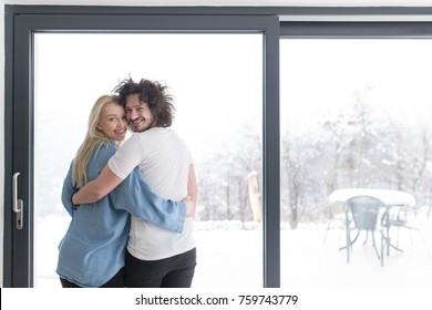 romantic happy young couple enjoying morning coffee by the window on cold winter day at home
