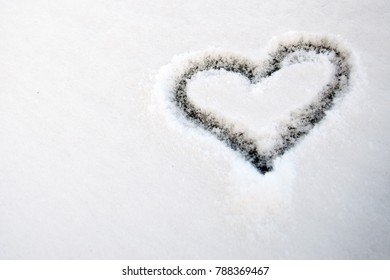 Romantic heart shape drawn to a car window with snow.