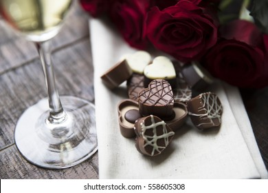 Romantic heart shaped chocolates with red roses and champagne.