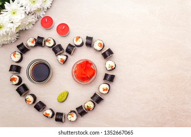 Romantic heart sushi dinner. Maki rolls with ginger, wasabi and soy sauce, candles and flowers. Concept for Valentine's Day or March 8th. Stone background, top view