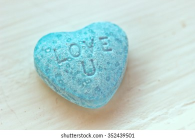 "Romantic heart-shape candy with label ""Love you"" on the white wood"