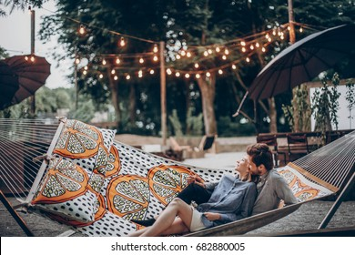 Romantic hipster couple enjoy rest on a hammock at  resort, cute woman lying with handsome man, lights in the background