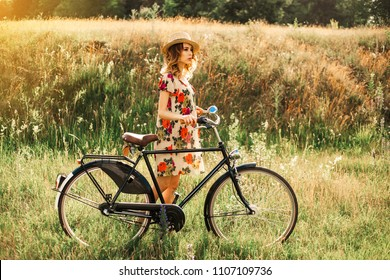 Romantic hipster girl on retro bike in the field, dressed in light summer dress with flowers and straw hat, summertime in boho style, modern retro