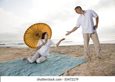 Romantic Hispanic couple together on beach