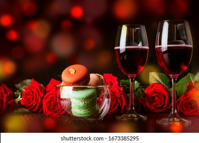 Romantic holiday, glasses with red wine and roses and macaroons