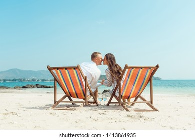 Romantic holiday travel. Portrait of happy young couple hugging near with deck chairs in luxury beach hotel near sea. Love and relationship concept. Summer vacation in tropical paradise island.