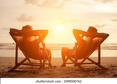 Romantic holiday travel. Silhouette of happy young couple sitting in deck chairs in luxury beach hotel at sunset near sea. Love and relationship concept. Summer vacation in tropical paradise island.