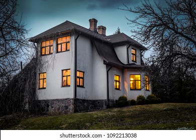 Romantic house with a light in the window. Night landscape.