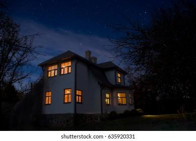 Romantisches Haus mit Licht im Fenster. Nachtlandschaft.