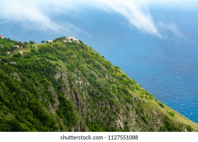 Romantic houses on the top of a cliff with a beautiful view of the sea. Located on the island of Saba, in the Caribbean. A small island with a rainforest, an oasis of peace. White houses wth red roof.
