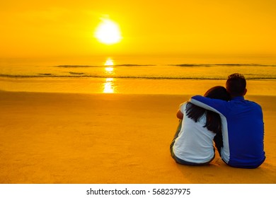 Romantic hugging Young couple watching the sunset on the beach