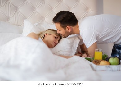 Romantic husband waking wife with breakfast in bed