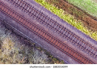 Romantic image of two railway tracks which consists of two parallel steel rails, anchored perpendicular to members called ties (sleepers) of concrete to maintain a consistent distance apart. Pattern.