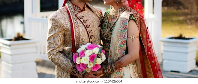 Romantic Indian couple holding wedding bouqet and posing wedding day