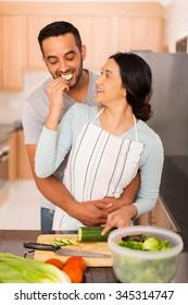 romantic indian woman feeding boyfriend slice of cucumber