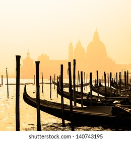 Romantic Italian city of Venice (Venezia), a World Heritage Site: traditional Venetian wooden boats, gondolier and Roman Catholic church Basilica di Santa Maria della Salute in the misty background.