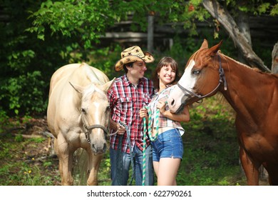 Romantic joyful  cowboy couple with hourses flirting and playing