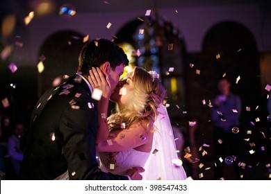 Romantic kiss of the bride and groom on the dancefloor