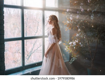 Romantic lady, blonde woman with long hair in white vintage dress stands in dark room, looks out window. Girl bride princess in wedding dress. Elegant hairstyle. Bright rays of sun concept of waiting.