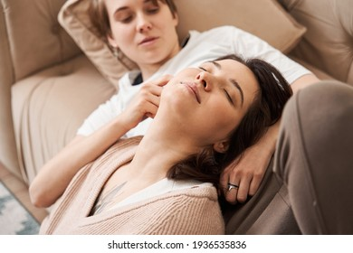 Romantic lesbian couple in love embracing and cuddling at the sofa