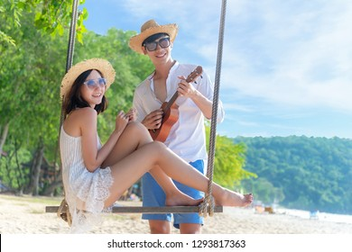 Romantic lifestyle asian couples lover playing an ukulele on the hammock. relax and honeymoon in luxury resort near the beach. Thailand. Summer,Travel, Valentine Concept.