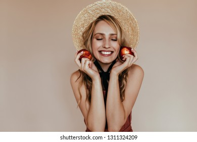 Romantic long-haired lady posing on beige background in straw hat. Ecstatic european young woman holding peach.