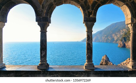 Romantic look at Portovenere on mediterranean sea through a historic medieval stone arch windows. Liguria . Italy