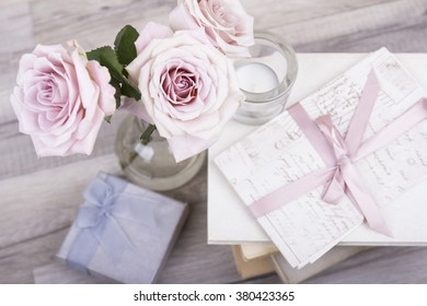 Romantic, love background. Pink roses in vase with books and letters