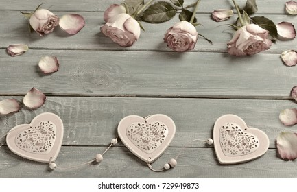 romantic love background with pink roses,petals and hearts lying on blue wooden planks