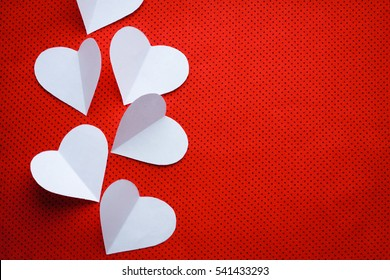 Romantic love concept background with copy space for text and three white paper hearts laying on a red textured background in a small black polka dots. Beautiful Valentines minimalist hipsters card.