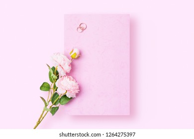 A romantic love letter that is yet to be written with wedding rings and rose on pink background. Flat lay image with copy space.