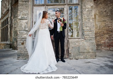 Romantic lovely newly married couple posing by the medieval castle on their wedding day.
