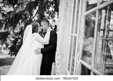 Romantic lovely newly married couple posing by the medieval castle on their wedding day. Black and white photo.