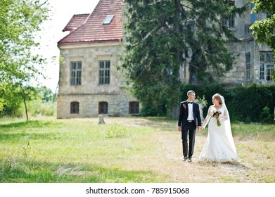 Romantic lovely newly married couple posing in the park by the medieval castle on their wedding day.
