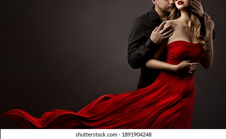Romantic Lovers Couple Dancing. Man hugging and kissing beautiful Woman in Silk Red flying Dress. Fashion Portrait. Studio Black Background