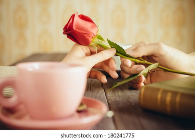 Romantic lovers dating. Love and flirt concept. Man giving rose to woman. Couple on secret dating at coffee shop.