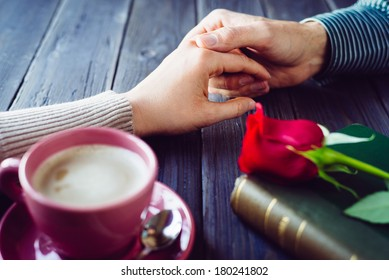 Romantic lovers dating. Male and female hands caressing with love. Couple on secret dating at coffee shop.