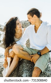 Romantic lovers hug and look each other in the eye near the sea