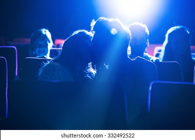 Romantic loving couple kissing at the cinema, love and relationships concept