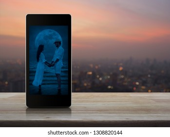 Romantic loving couple standing and holding hands together on modern smart mobile phone screen on table over blur of cityscape on warm light sundown, Internet dating online, Valentines day concept