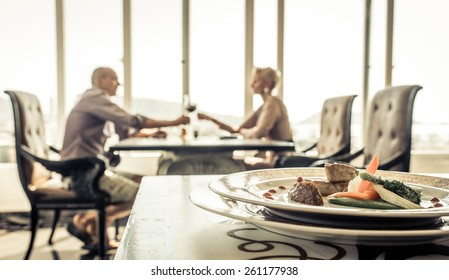romantic lunch at the restaurant. couple making toast with red wine.straight focus on the  plate with food on the front table