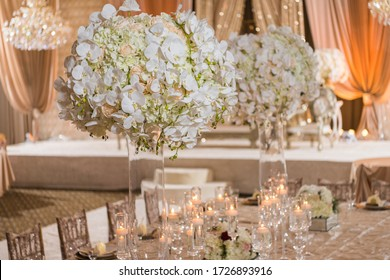 Romantic lush floral white orchids, pink flowers and hydrangeas styled in centerpieces for a wedding and accented with glowing votive candles
