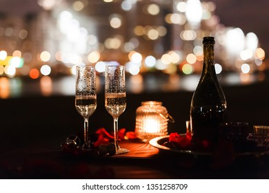 Romantic luxury evening with champagne setting with two glasses. rose petails and candles. Champagne for romantic celebrations or New Year party and enjoy for special moments. Bokeh background.