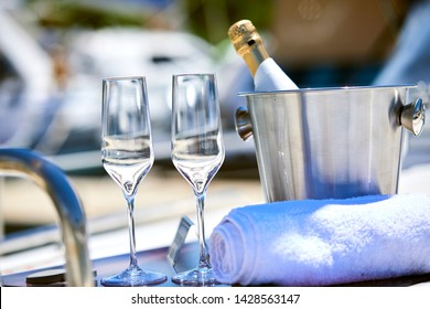 Romantic luxury evening on cruise yacht with champagne setting. Empty glasses and bottle with champagne and tropical sunset with sea background