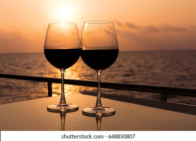Romantic luxury evening on cruise yacht with winery setting. Glasses, red wine and tropical sunset with sea background, nobody.