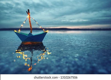 romantic magic winter evening at the lake with blue boat