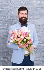Romantic man with flowers. Romantic gift. Macho getting ready romantic date. Waiting for darling. Tulips for sweetheart. Man well groomed wear tuxedo bow tie hold flowers bouquet. Invite her dating.