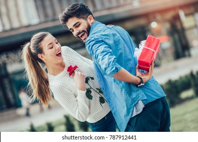 Romantic Man giving flower and gift box to woman for valentines day