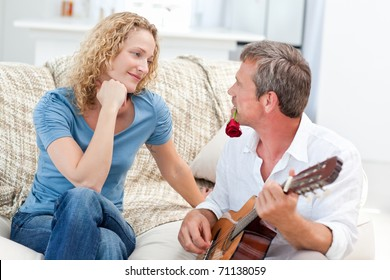 Romantic man playing guitar for her wife at home